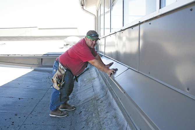 John Johnson with Stryker Sheet Metal installs siding at Dallas High School Monday. More similar projects will take place if voters approve an up-to $17 million bond this fall.