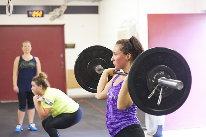 From left, Kala Garibay and Jessica Holbrook go through their workout routines Friday at Harvest CrossFit in Dallas as instructor MacLarin Jones, standing, observes.