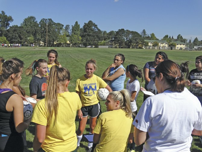 Seventh-graders gather around coach and English teacher Alisha Bowen on Thursday for the practice schedule.