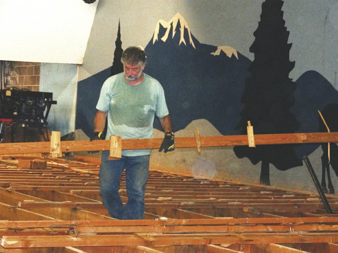 Calvary Church member Phil Bruner removes old bowling lanes to help convert the former Pioneer Lanes into the church's new home. Work started Aug. 20.