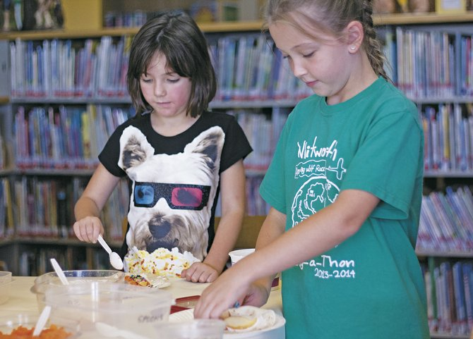 Emma Irwin, left, and her sister Jaden Irwin prepare healthy after-school snacks at the Dallas Public Library the afternoon of Sept. 3. They combined cream cheese, apples — and a small spoon of sprinkles — and rolled it all up in a tortilla. The sisters were part of a number of youngsters and their parents who took part in the lesson in making healthier food, one of the library's childrens' activities.