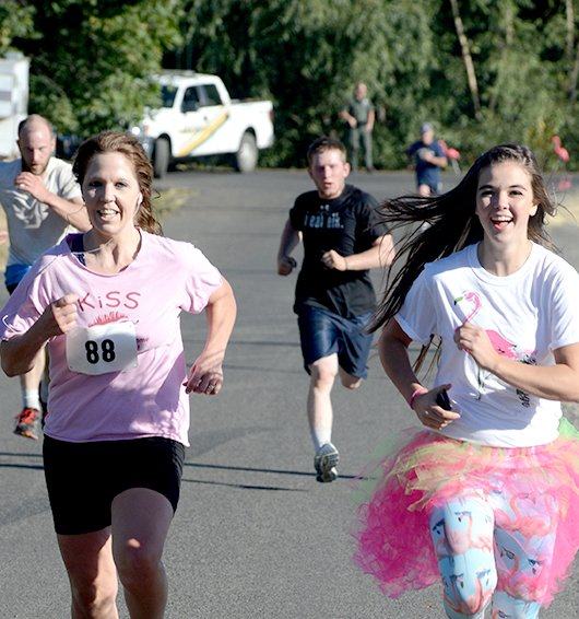 Flamingo Fun Run organizer Addie Lutz (right) races participant Melinda Wimer to the finish line during the 5K race held last Saturday, Sept. 23 at Lions Park.