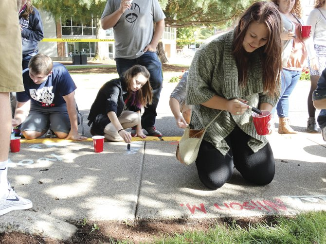Allison Myers of Veneta signs her name on the sidewalk at Western Oregon University on Friday. Evidence of the tradition of students putting their name on the walkways of campus can be seen along the pathways surrounding the Werner Center.