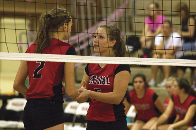Central's Kylie Nash (right) and Julia Kenyon talk while waiting for a serve against Dallas on Monday.