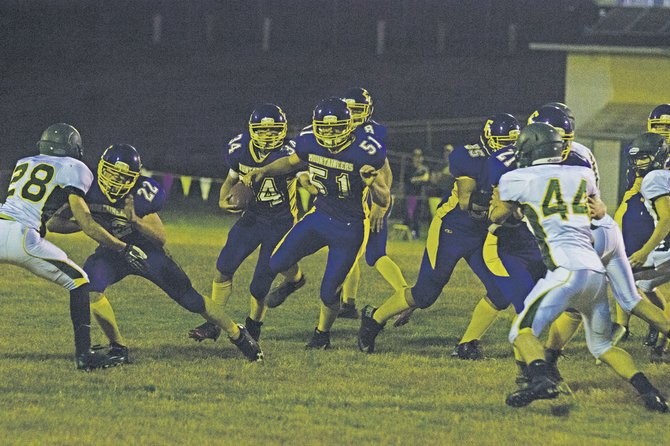 Arlin Schwanke (51) tries to clear a path for Zach Weems (34) against Triangle Lake on Friday.