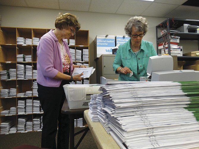 Sharon Smith, left, checks ballot envelopes for precinct number while Carol Gagznos, right, readies the envelope opener on Tuesday to start the ballot counting process.