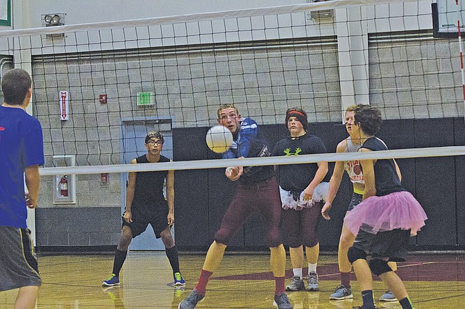 """Senior David Silver (second from left) looks to hit the ball during Perrydale High's Macho Man volleyball game on Oct. 21. The annual tradition features the seniors and freshmen against the sophomores and juniors, which was followed by a powderpuff football game. The school celebrated homecoming week with a """"superhero"""" theme."""