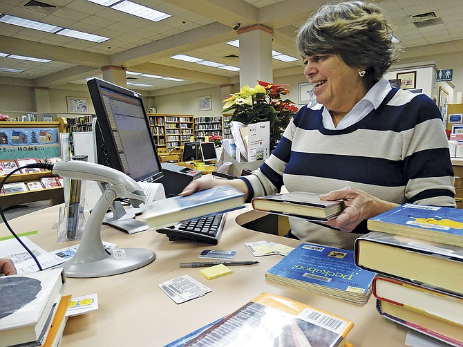Nancy Woolsey, Dallas Library tech assistant, practices scanning books to see if they are in the new system.