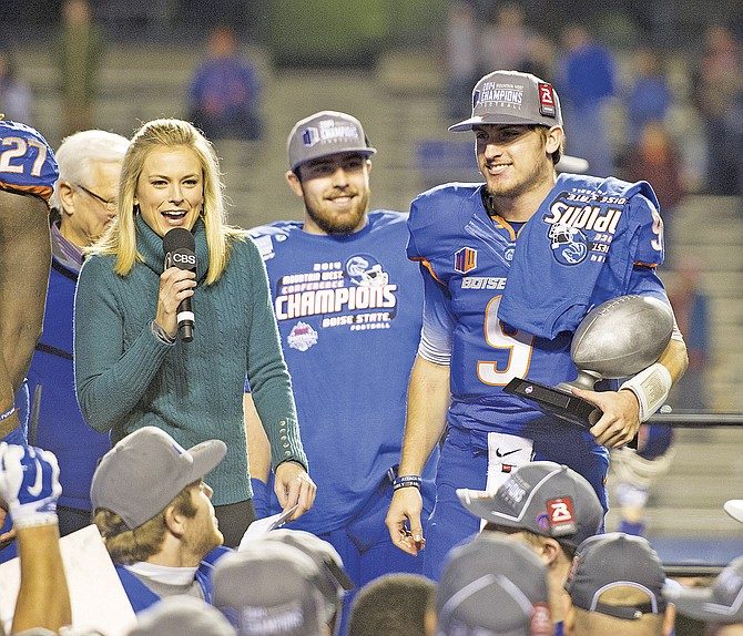 Senior quarterback Grant Hedrick (right) celebrates winning the Mountain West Conference Football Championship on Saturday evening.