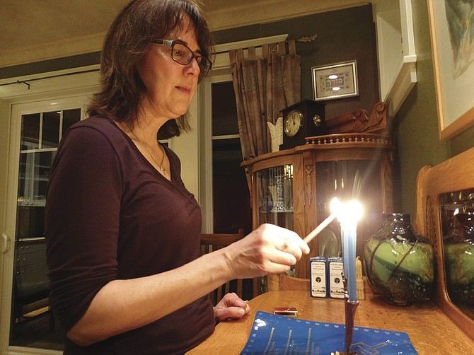 Francine Shetterly lights the menorah using the shamash, or helper candle. Each night of Hanukkah, a candle is added, symbolizing the miracle that one  day's worth of oil lasted the Maccabees eight days.