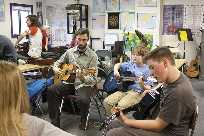 Joaquin Dollar, left,  leads students Colin Lyday, center, and August Bobier, right, through a  lesson during a guitar class at Kings Valley Charter School on Dec. 10. Dollar has been teaching music at the school since Nov. 1 through a partnership between music education nonprofit Ethos and AmeriCorps. He will work  at the school through the summer and hopes to provide private lessons to students.