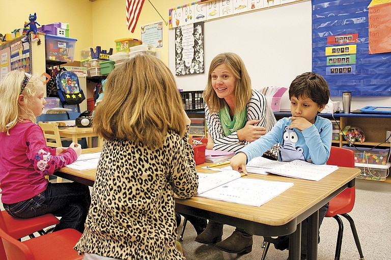 Monmouth Elementary School teacher Samantha Henderson works with students in her morning kindergarten class.