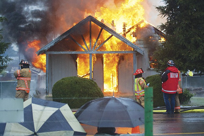 "It was fire and rain Saturday afternoon as Dallas firefighters trained in a ""burn to learn"" in Dallas. Onlookers huddled under umbrellas, watching the small house burn."