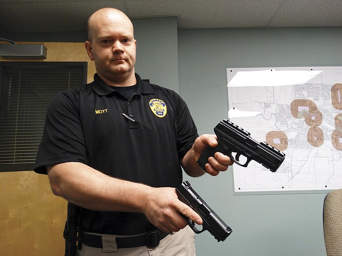Lt. Jerry Mott holds two weapons — one real, one fake. The one in his right hand is real. The replica gun in his left hand was confiscated as evidence in a crime.