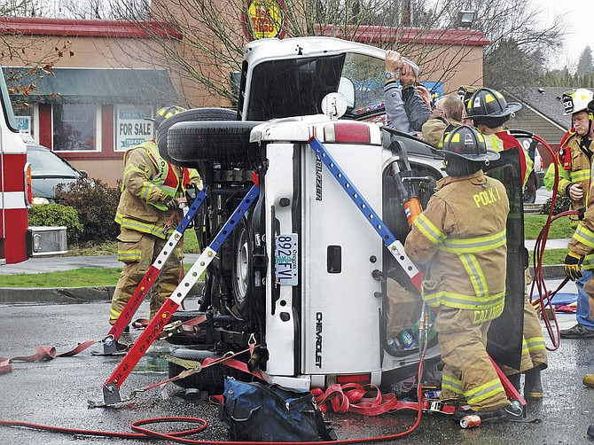 Firefighters from Polk Fire District No. 1 work to remove the top of a Chevy Blazer to extricate the passenger and driver after an accident on Saturday.