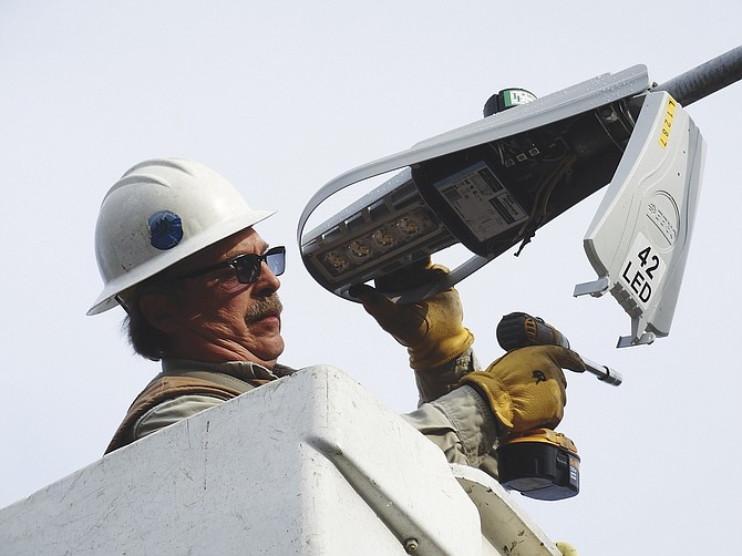 Russ Downer installs a new LED light on a streetlight in the neighborhood of Candlewood Way. The new lights give off a clearer, whiter light than the old ones, and use less energy.