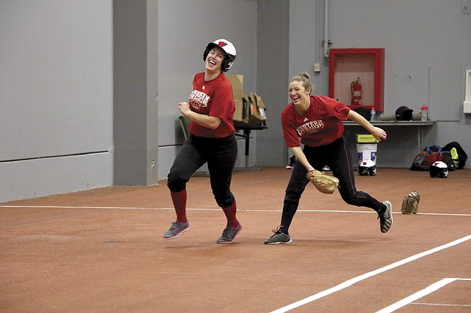 Senior pitcher Jourdan Williams (left) and senior outfielder Amanda Evola have a good laugh during practice. The duo hopes to lead WOU to a second conference title.