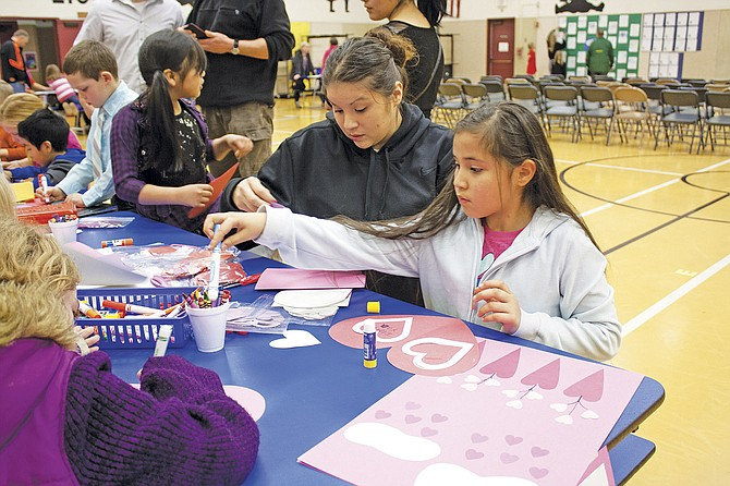 """First-grader Leah Reyes, with her mother Ellena Reyes, designs a handmade Valentine's Day card Thursday at Lyle Elementary School's """"Celebration of Writing Night."""" The event was created to put student writing on display, as well as encourage parents to play writing games with their children at home. Writing night consisted of selected students reading their stories aloud and several stations with creative writing activities for students and their families to participate in."""