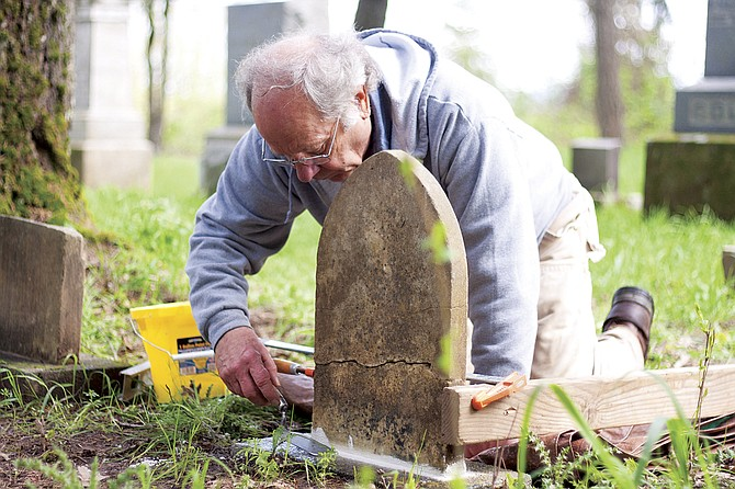 Lloyd Collins repairs a headstone in a pioneer cemetery south of Monmouth. He was the lone member of the Polk County Cemetery Savers volunteer group working Saturday morning on cleaning and restoring headstones and cataloguing burials in Chamberlin Cemetery. This is the sixth cemetery the group has worked on since beginning with Hart Riggs Cemetery between Falls City and Dallas in 2012.