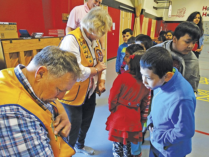 Lions Steve Moser and Kathy Zehner explain what badges and pins on their Lion's jackets mean to a group of first- and second-graders at Independence Elementary School on Friday morning. The Lions presented IES Principal Steve Tillery (not pictured) with four Kindles, purchased with club funds. Each year the Central Lions Club chooses a school to donate to.