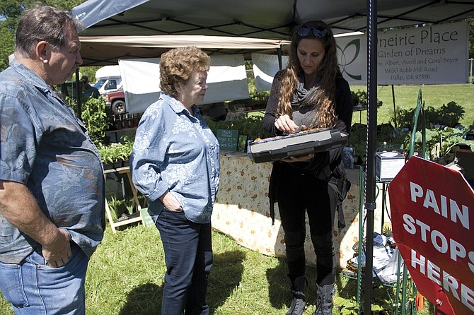 Averil Beyer with Oneiric Place, a Dallas farm, shows customers her orgonite stones during opening day of the Polk County Bounty Market in Dallas. The market is now open for the season on Thursdays running through September at the Academy Building.