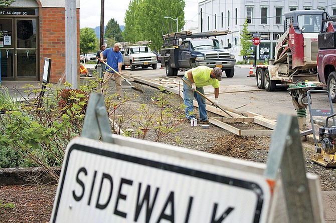 A crew with Dallas-based Evander Concrete prepares the sidewalk on Southeast Court Street for new concrete on Friday. The new sidewalk was installed over the weekend as part of an ongoing Dallas Urban Renewal Agency project.