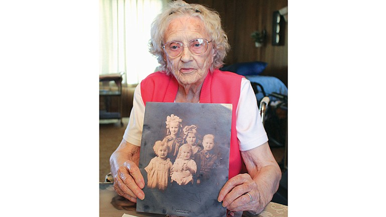 Pauline Padgham Shockley was the eldest of nine children born to Sunnyside pioneers Herbert and Gertrude Padgham. Here, she holds a photograph of herself with four of her siblings. She is the tall girl in the back with the blonde curls and big white bow. Also pictured with her are (back row L-R) Roxine, Paul; and (front L-R) Berdina and David.