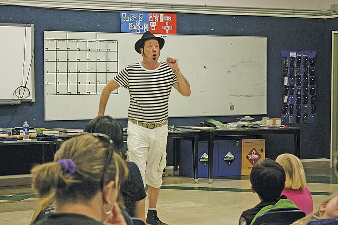 """Acclaimed storyteller Christopher Leebrick acts out a story Thursday at Wagner Community Library in Falls City. Leebrick visited the library as part of the  statewide """"Save for College, Save the Day!"""" program encouraging kids to keep reading during the summer."""