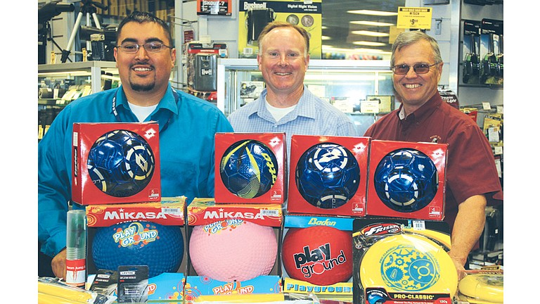 Sunnyside Big 5 Sporting Goods Store Manager Abel Orosco, left, presents discounted sporting goods to Randy Bauman, middle, and Gary Christensen of the Central Washington Chapter of Safari Club International.