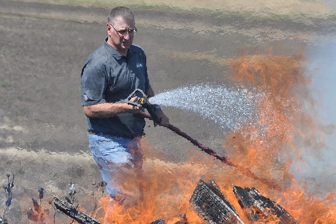 GRFD firefighter Ron Funke hits a pile of flaming debris with water at a field blaze Wednesday morning, July 1, at the U.S. Highway 95 and Johnston Road intersection south of Grangeville.