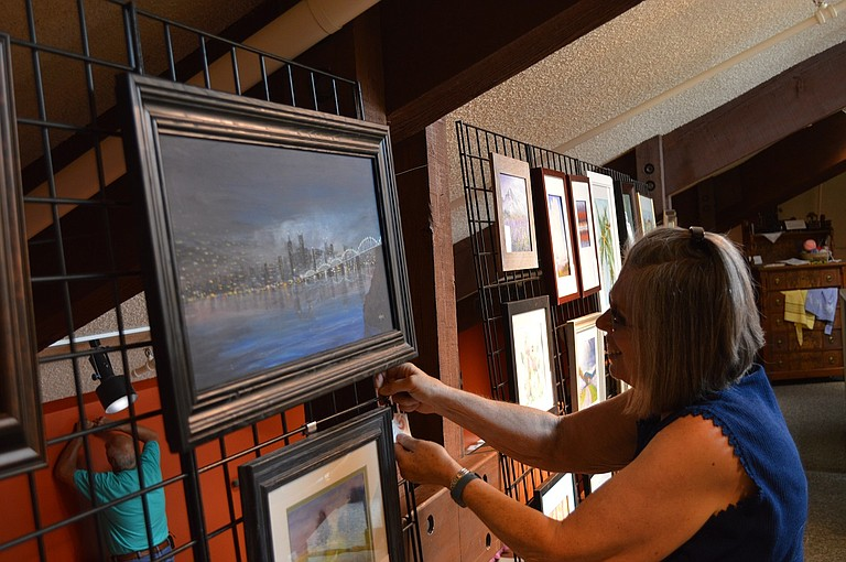 The History Museum is hosting an art exhibit through July 18. Art club member Joyce Uczen hangs works in the mezzanine of the museum, located at 300 E. Port Marina Drive, next to the marina.