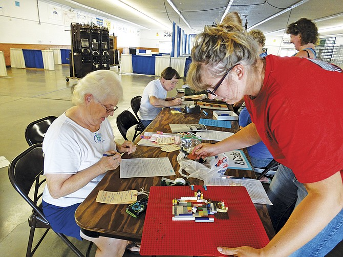 Jayne Domes, of Sheridan, fills out the paperwork for children's arts and crafts open class entries at the Polk County Fair on Monday. Ilene Lewis, a volunteer for the fair, helps keep everything straight with tags for each exhibit.