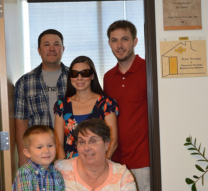 TAMURA family gathers in the room at The Next Door Inc., on Tucker Road, named in Ken Tamura's honor. With Nancy are her grandson, Asher, son, Trevor, and daughter Trista and her husband, Greg Guenther.