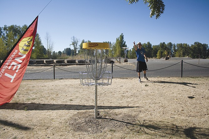 Hayden Rue shows off one of the holes at Independence's disc golf course at Riverview Park.