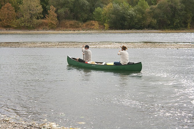Ryan Kelley, front, and Brad Ford, back, launch their journey to Portland from Independence on Saturday. The cargo in their canoe includes Project 1899 pinot noir, a special vintage made without electricity or modern technology.