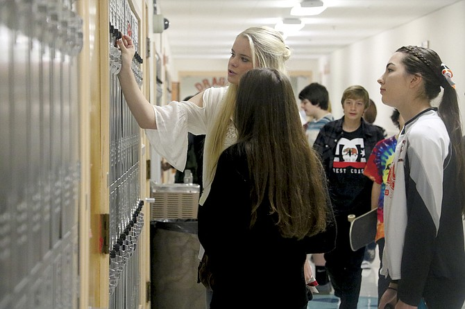 Mikela Bruer helps Emi Olbregts with her locker during Dallas High School's first day of school on Tuesday.