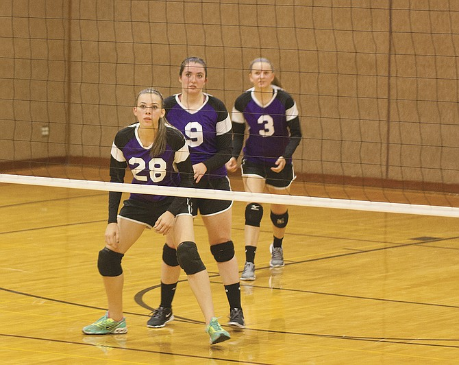 Maddy Hendrickson, Allison Kidd and Tiaunnah Davis await a point during Falls City's victory over Jewell.
