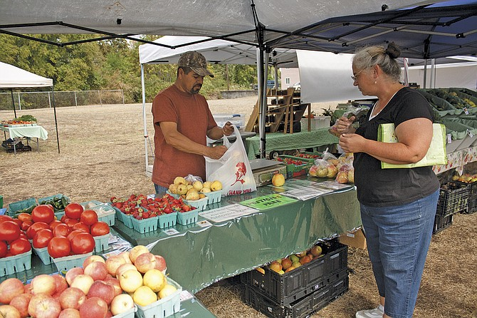 Tony Diaz bags up some of his fresh produce at the Polk County Bounty Market in Dallas on Thursday. This is the last week for the market before it closes down for winter, to return next spring. The market is at the corner of Academy and Main streets.