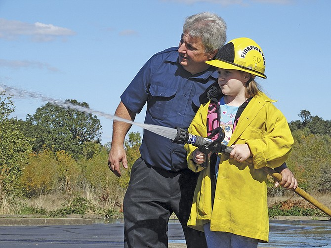 Volunteer firefighter Carlo Calabrese, left, helps Kami-Lea Barggraf, 7, of Independence take a turn using a fire hose during the Polk County Fire No. 1's open house on Saturday. Attendees had the chance to meet firefighters, ride an engine and tour an air ambulance.