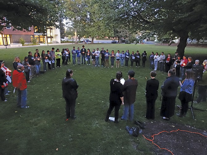More than 60 students, faculty and staff at Western Oregon University gathered Saturday for a candlelight vigil in support of the victims and survivors of a mass-casualty shooting at Umpqua Community College.