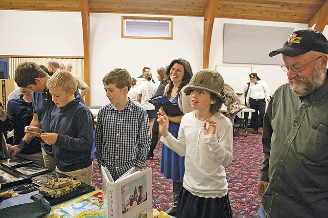 Faith Christian School fifth-grader Jessica Stoddard, second from right, tries on a military helmet Friday at a veteran's celebration and brunch at the Dallas school. Veterans gave presentations, including teaching the students how to properly salute, answered students' questions and were treated to brunch at the school.