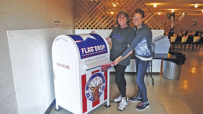 Kathy Martin-Willis and Dori Showell drop an old, faded U.S. flag into the new drop box to be retired properly.