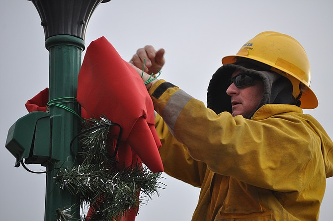 An Avista crew was assisting volunteers Friday, Nov. 13, in putting up 50 new lighted Christmas garlands on lampposts along Grangeville's Main Street.