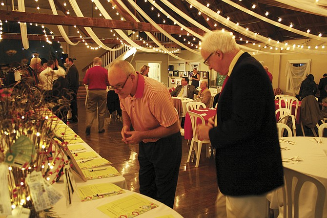Mike Ainsworth decides what silent auction items to bid on at last year's Monmouth Independence YMCA Christmas auction at Green Villa Barn.