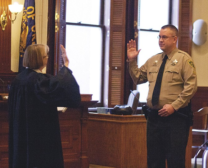 Polk County Circuit Judge Sally Avera swears in new Polk County Sheriff Mark Garton on Monday during a ceremony at the Polk County Courthouse. Garton was appointed to the office temporarily and is running for election to hold the job permanently.