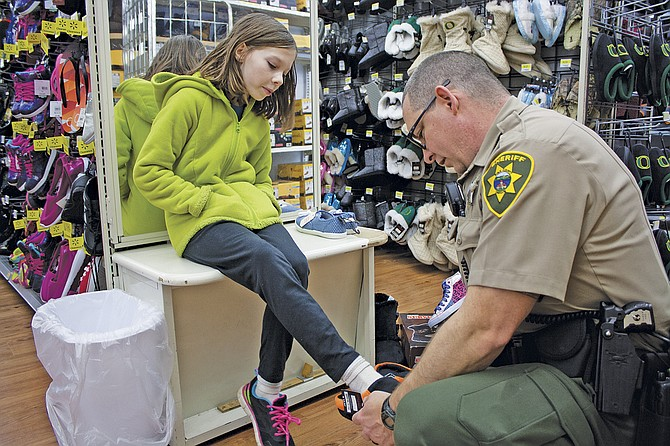 Polk County Deputy Marty Watson helps Katelynn Ross pick out slippers at Wal-Mart in Dallas on Saturday. Polk County Sheriff's Office employees helped children from Falls City pick out gifts for  their families during the annual Christmas shopping spree, a partnership between Wal-Mart, Polk County and the sheriff's office.