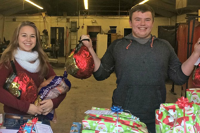 Contributed photo Grangeville High School students Maggie Chmelik and Jon Asker help load food and gifts collected by GHS FFA. FFA adopted three local families for Christmas.