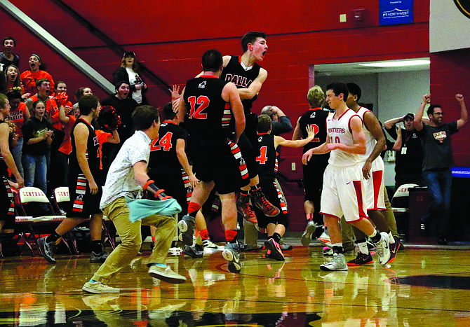 Dallas players celebrate moments after Everett Minahan hit a half-court shot at the end of regulation to tie Central at 34 on Jan. 12. The Dragons won 38-37 in overtime.