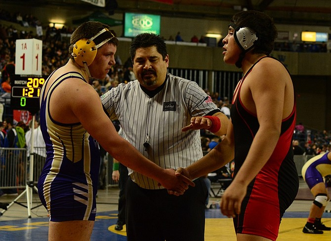 CHS sophomore Alex Medina (right) shakes hands with Goldendale 220-pounder Cameron Read after Read ended Medina's first state tournament with a 7-0 victory.