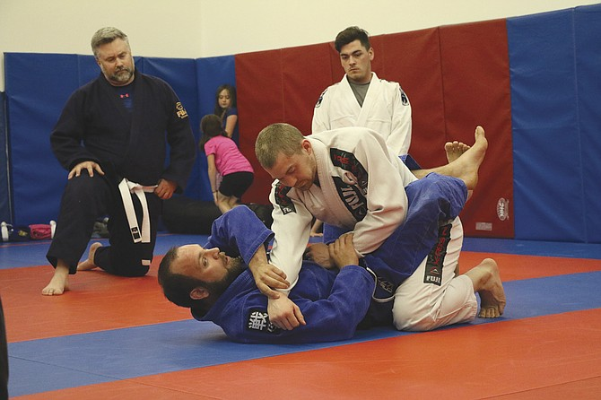 Daniel Priebe (blue) demonstrates a move during a class on April 13.